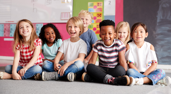 kids sitting on a floor in a classroom smiling